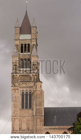 Brugge Belgium - August 10 2016: The brick square tower of Sint Salvator Cathedral stands against stormy rainy dark sky.