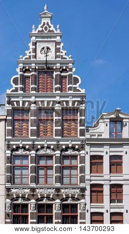 Amsterdam the Netherlands - August 16 2016: Historic facade of cheese shop on Damrak displays racks of cheese in front of windows set in white and dark wall decoration. Previously a book store. Blue sky.