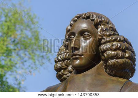 Amsterdam the Netherlands - August 16 2016: The famous philosopher Baruch Spinoza has his statue near the Bijvoetbrug. Detail of bronze shows serious looking man with long curly hair.