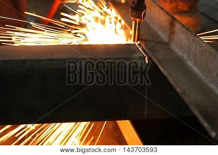 Worker cutting a steel in the factory