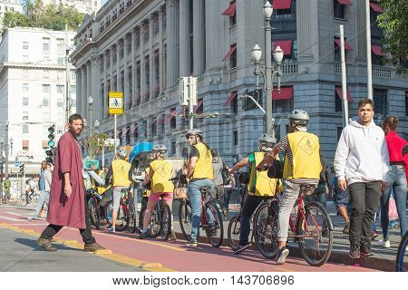 Man With Red Tunic (left) In Hot Day Carrying A Pepper Standing Toward The Group Of Cyclists In Fron
