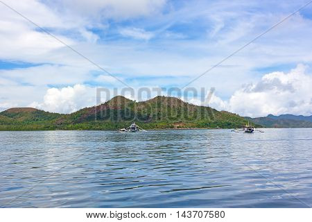 Traditional Pilipino boats in lagoon of Coron Island Palawan province Philippines. Scenic view from the water on Coron Island landscape.