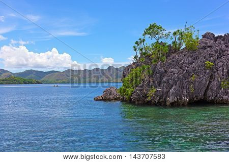 Sea waters of Coron Island lagoon with mountains on horizon Philippines. Tropical island landscape with the boats in a view.