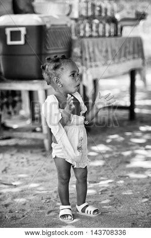 KARA, TOGO - MAR 9, 2013: Unidentified Togolese girl claps her hands in the street. Children in Togo suffer of poverty due to the unstable econimic situation