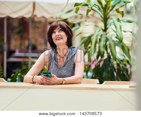 Portrait of woman sitting at cafe and using her smartphone while writing text on mobile