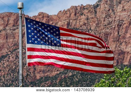 Old Glory Waying in the Breeze in Front of a Beautiful Rock Formations in Zion National Park Utah.