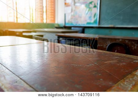 old dirty wooden desk in classroom with chalkboard