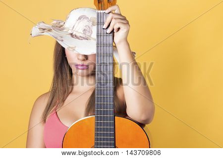 Woman wearing a hat hiding her eyes holding a acoustic guitar in studio over a yellow background. Selective focus focus on her face.
