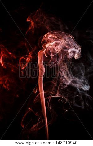 Abstract art. Color crimson smoke from the aromatic sticks on a black background. Background for Halloween. Texture fog. Design element. The concept of aromatherapy.