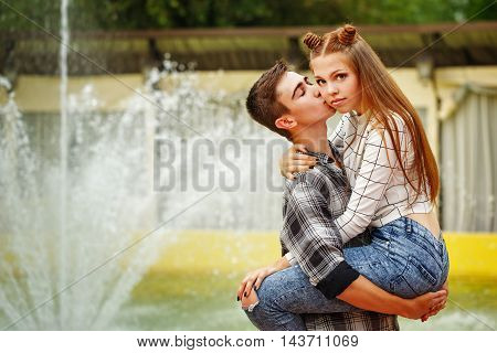 Enamoured teenagers embrace. Girlfriend and boyfriend strolling in a city park. A boy holding the girl in his arms and kisses her on the cheek. First love. He falls in love. Date.