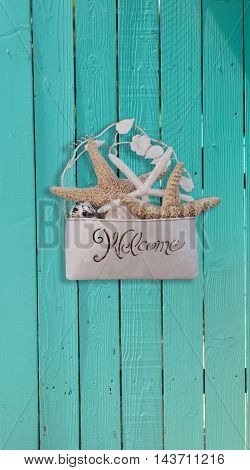 Starfish and seashell welcome basket decor on an aqua blue door in summer on Cape Cod