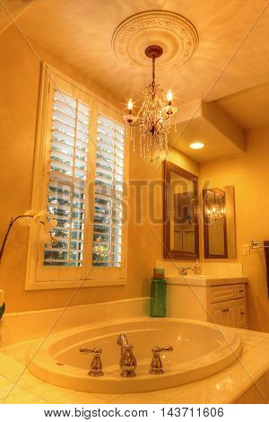 Irvine, CA, USA - August 19, 2016: Oval hot tub spa bathtub in a marble bathroom with feng shui decor and chandelier.