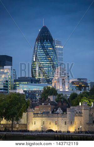 LONDON, UK - SEPTEMBER 19, 2015: City of London with first night lights at sunset. Modern business and banking aria. View from the Tower bridge include  Gherkin building