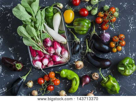Fresh vegetables - radishes tomatoes peppers onions garlic eggplant on a dark background top view. Raw ingredients for cooking
