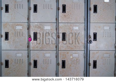 A perspective view of a stack of grey metal school lockers with combination locks