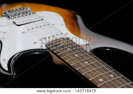 electric guitar isolated on dark background .