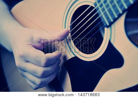 Hands playing acoustic guitar close up .