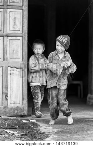 TA PHIN, VIETMAN - SEP 12, 2014: Unidentified boys come out of the door in the village of Vietnam. Red Dao is a minority ethnic group of Vietnam