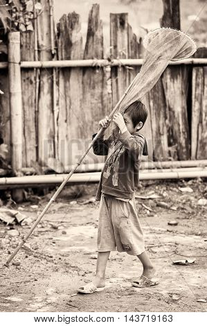 TA PHIN, VIETMAN - SEP 12, 2014: Unidentified boy runs with a fish net in the village of Vietnam. Red Dao is a minority ethnic group of Vietnam