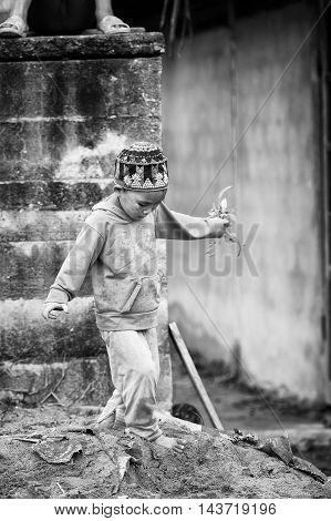 TA PHIN, VIETMAN - SEP 12, 2014: Unidentified boy runs  in the village of Vietnam. Red Dao is a minority ethnic group of Vietnam