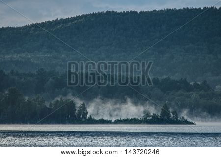 Morning Mist Rises Above The Surface Of Forest Lake