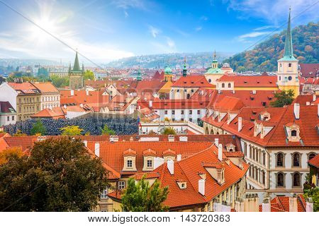 Aerial view of old Red Tiles roofs in the city Prague, Czech Republic, Europe. Beautiful Autumn day with blue sky with clouds in the town.