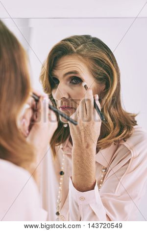 Middle-aged woman applying eyeshadow in the morning