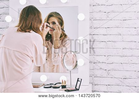 Mature woman getting ready in front of mirror