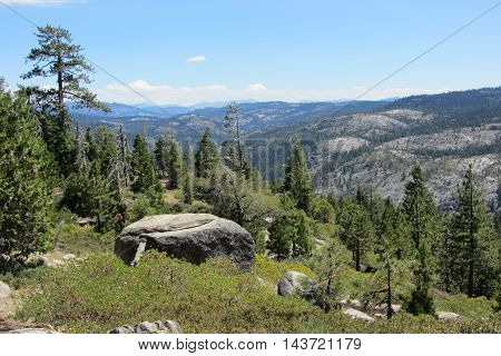 View of Sierra Nevada Mountains with boulder and trees, from California Highway 4 bear Lake Alpine