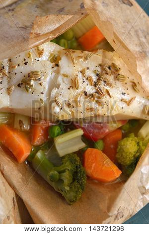 White fish fillet baked in paper parchment with vegetables