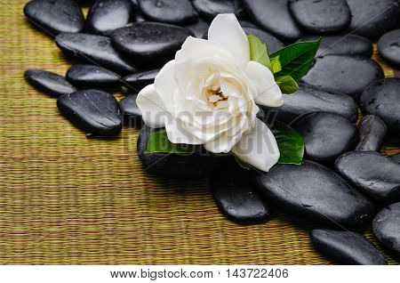 stones and gardenia on mat