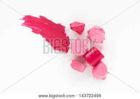 Cut pink lipstick with smear of one, flat lay. Close-up of damaged female cosmetics, top view on colorful rosy rouge, copy space, white background