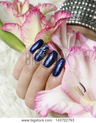 Beautifully manicured fingernails with gladiolus flowers in the background
