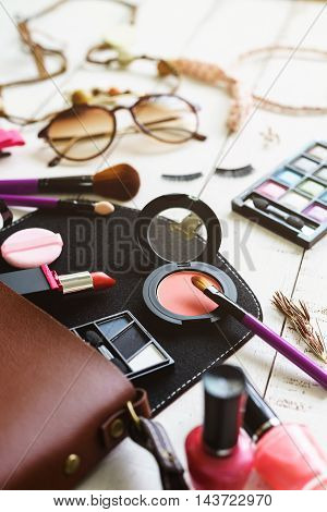 various makeup products and accessories on white wooden background