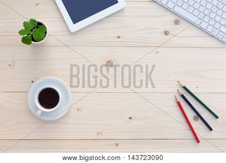 Top View of White Office Desk with Modern Electronics Computer Keyboard Tablet Notepad Color Pencils Coffee Cup and Green Flower