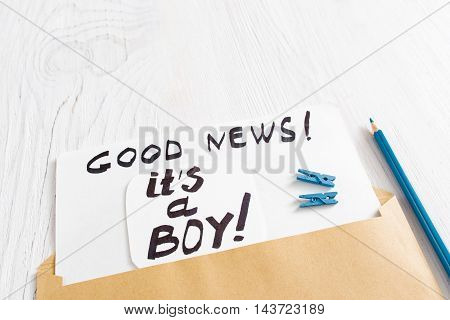 Card it's a boy with blue pins and pencil, close-up. Note with congratulation about newborn child gender, white wooden background, free space