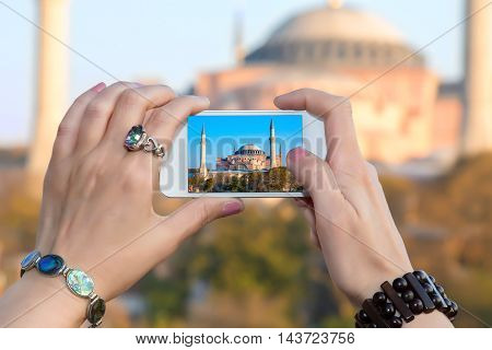Woman taking Photo with camera phone in Istanbul city female hands with fashion jewellery bracelets  holding white telephone with Picture of famous attraction view