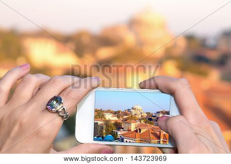 Me taking Photo with camera phone in Istanbul city female hands holding white telephone with Picture of famous attraction view
