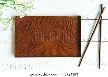 Empty wooden plate with chopsticks on white wooden table, Top view