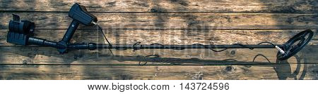 Old and retro metal detector on wood background