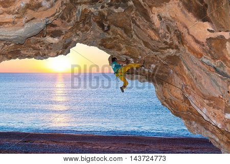Strong Male Rock Climber ascending dangerous rocky Roof Sea Beach Luminous Sunrise Background