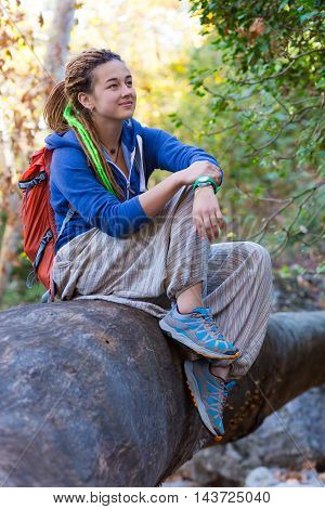 Joyful Girl with Backpack and Hippie style casual sporty clothing sitting on large trunk of a fallen Tree in Forest and enjoying Nature