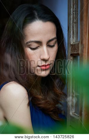 young skinny woman looking down from window
