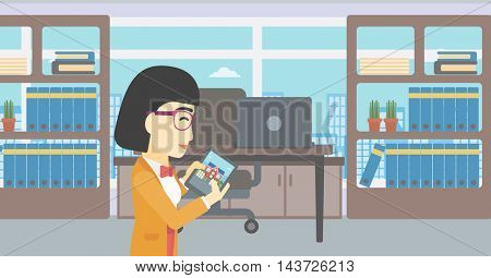 An asian woman looking at house on a digital tablet screen. Young woman standing in office and looking for house on tablet computer. Vector flat design illustration. Horizontal layout.