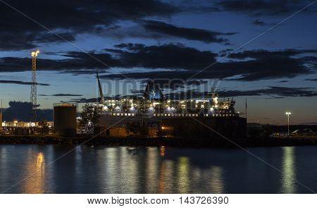 UMEA, SWEDEN ON AUGUST 03. View of a ferry in harbor in the night on August 03, 2016 in Umea, Sweden. Nordic summer night, lights from the ship, reflexing in the water. Editorial use.