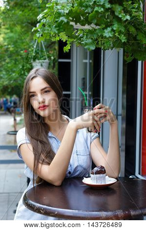 Thoughtful beautiful girl in outdoor cafe drinking coffee with muffin