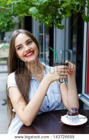 Smiling beautiful girl in outdoor cafe drinking coffee with muffin