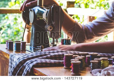 Young girl sews on the old sewing machine