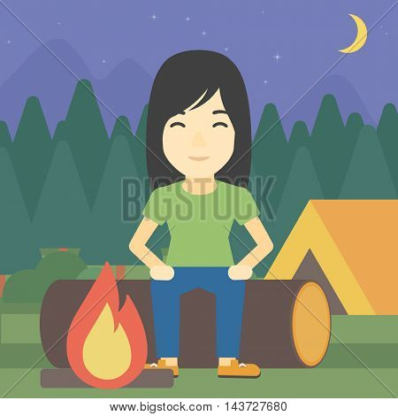 An asian woman sitting on a log near a fire on a background of camping site with tent. Woman sitting near a campfire at a campsite. Vector flat design illustration. Square layout.