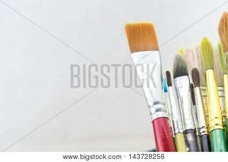 Group Of Used Brush In Bucket On Grey Background